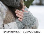 hands in woolen mitts with a... | Shutterstock . vector #1229204389