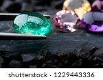 The emerald gemstone jewelry photo with black stones and dark lighting.