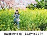 woman take a sakura cheery... | Shutterstock . vector #1229463349