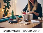 young woman wrapping gifts for... | Shutterstock . vector #1229859010