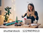 happy young woman wrapping gifts | Shutterstock . vector #1229859013
