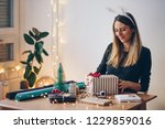 happy young woman wrapping gifts | Shutterstock . vector #1229859016