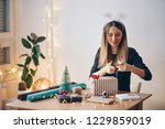 happy young woman wrapping gifts | Shutterstock . vector #1229859019