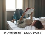 teen girl in sweater reading a... | Shutterstock . vector #1230019366