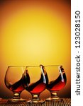 Three glasses of cognac on yellow background with splash - stock photo