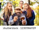 Forest team. Cheerful happy children standing behind their teacher while looking at him taking photos of mushroom