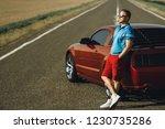 A man near the red sportscar on ...
