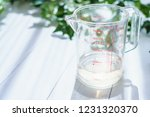 measuring cup on wooden board   Shutterstock . vector #1231320370