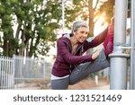 senior woman using lamp post as ... | Shutterstock . vector #1231521469