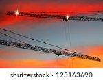 Construction cranes on sunset bright background - stock photo