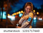 young woman  running at night... | Shutterstock . vector #1231717660