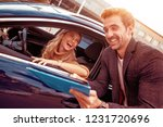 happy woman with car dealer in... | Shutterstock . vector #1231720696