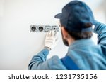 electrician in uniform mounting ... | Shutterstock . vector #1231735156