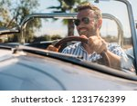 man driving a convertible... | Shutterstock . vector #1231762399