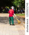 woman sweeping on the pavement... | Shutterstock . vector #1232021743