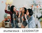 Small photo of young girls best friends celebrating graduation party in house. female students playing with whistles and balloons having fun at decorated home. enjoyment friendship never end concept.