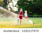 Kids play with water on hot summer day. Children with garden sprinkler. Outdoor fun. Boy and girl run on football field after training under water drops. - stock photo