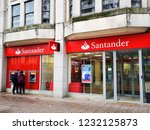 Small photo of Cardiff, UK: November 16, 2018: Two people use the cash point outside a bank. Santander UK plc is a British bank, wholly owned by the Spanish Santander Group.