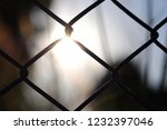 chain link fence and a sunrise... | Shutterstock . vector #1232397046