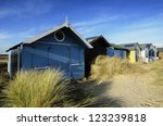 beach huts in sand dunes at...