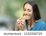 happy woman eating and looking... | Shutterstock . vector #1232530729