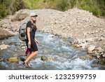 attractive woman hiking across... | Shutterstock . vector #1232599759