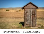 Wooden Outhouse On The Edge Of...