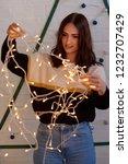 woman putting up christmas... | Shutterstock . vector #1232707429