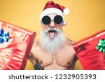 Small photo of Tattooed fit santa claus doing crazy and giving christmas gifts - Trendy beard hipster senior wearing xmas clothes and holding presents - x-mas Celebration and holidays concept