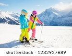 child skiing in the mountains.... | Shutterstock . vector #1232927689