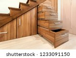 Small photo of Modern architecture interior with luxury hallway with glossy wooden stairs in modern storey house. Custom built pullout cabinets on glides in slots under stairs