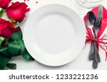 Stock photo valentine s day romantic tabble setting with red roses plates cutlery on white background empty 1233221236