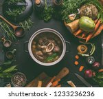 Cooked beef meat shin with bone in cooking pot on dark kitchen table background with low carb vegetables and spices ingredients for soup, top view. Meat broth or stock. Clean low-calorie food concept