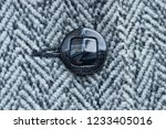 black button on woolen striped... | Shutterstock . vector #1233405016