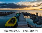 Peaceful sea cloudy sunset dramatic sky and wooden pier boats - stock photo