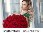 Stock photo elegant beautiful blonde woman is wearing green fashion dress in cafe holding with big bouquet of 1233781249