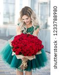 Stock photo elegant beautiful blonde woman is wearing green fashion dress in cafe holding with big bouquet of 1233788980