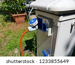 AC power sockets at a camping site, Full service campground electricity with camper motor home in background - stock photo