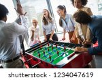 employees playing table soccer... | Shutterstock . vector #1234047619