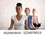 Small photo of Group diverse young beautiful women sitting in lotus position meditating during session at yoga studio. Girls practising exercises visualizing calming the brain increasing awareness and attentiveness
