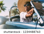 black woman driving a vintage... | Shutterstock . vector #1234488763