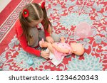 a little girl in red is played...   Shutterstock . vector #1234620343