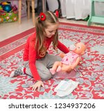 a little girl in red is played...   Shutterstock . vector #1234937206