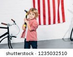cheerful curly boy holding... | Shutterstock . vector #1235032510