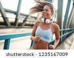 happy female runner jogging... | Shutterstock . vector #1235167009