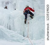 An ice climber makes his way up on a frozen waterfall near Prags, South Tyrol, Italy. - stock photo