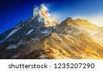 hiker reaches the mountain peak ... | Shutterstock . vector #1235207290