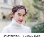 Stock photo head shot of beautiful young brunette woman smiling at camera outdoor fashion portrait of glamour 1235321686