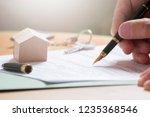 man hand signing documentation... | Shutterstock . vector #1235368546