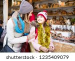 happy american female customers staring at counter of kiosk with figures for creating  miniature Christmas scenes